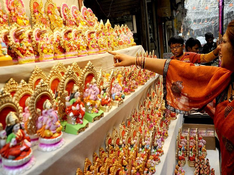 A woman looks at idols of deities at a roadside stall in New Delhi on the eve of Diwali. HT/Saarthak Aurora