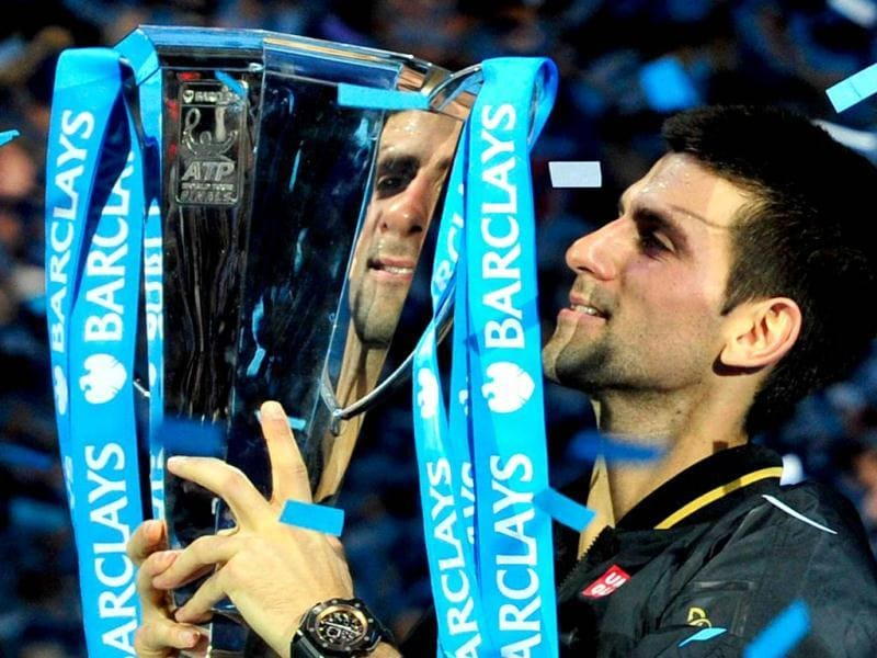 Serbia's Novak Djokovic poses with the winners' trophy after the singles final against Switzerland's Roger Federer on the eighth day of the ATP World Tour Finals tennis tournament in London. (AFP Photo)