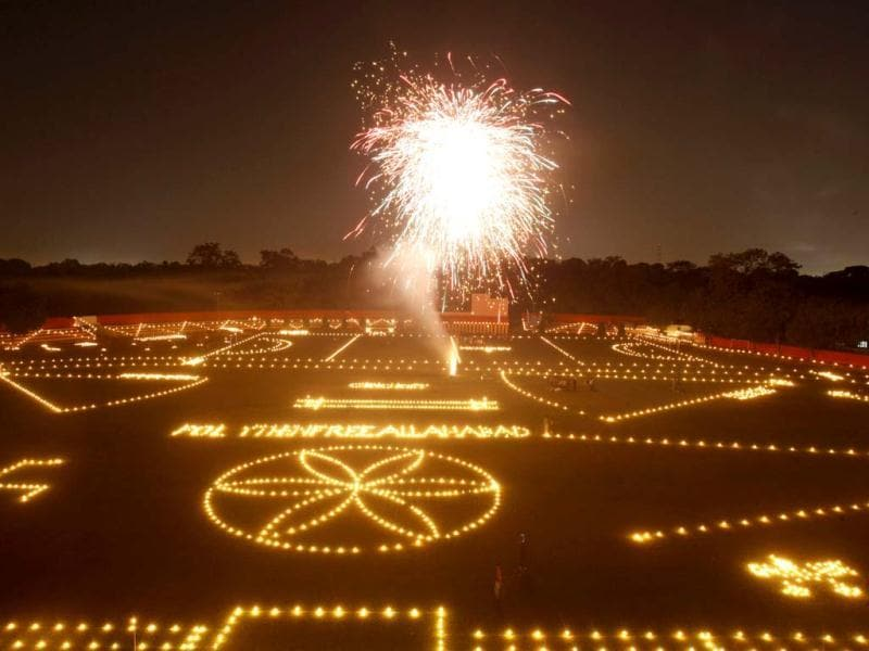 A firecracker lights up the sky as candles and lamps are seen lit across a field ahead of Diwali, the Hindu festival of lights. (AP Photo)