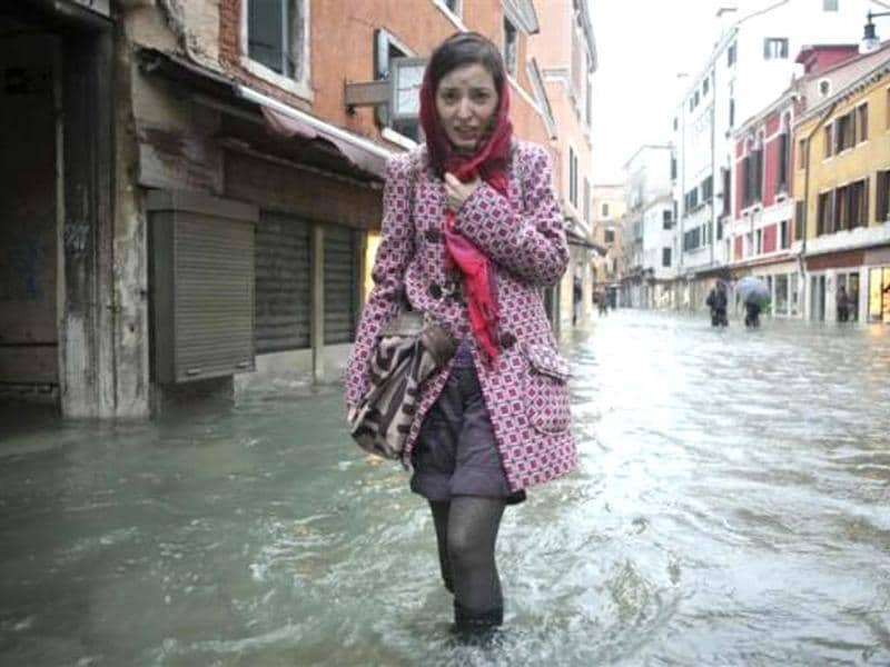 A woman walks in a flooded street during a period of seasonal high water in Venice November 11, 2012. Reuters/Manuel Silvestr