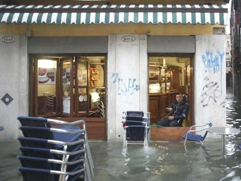 A man rests in a shop in a flooded street during a period of seasonal high water in Venice November 11, 2012. Reuters/Manuel Silvestri