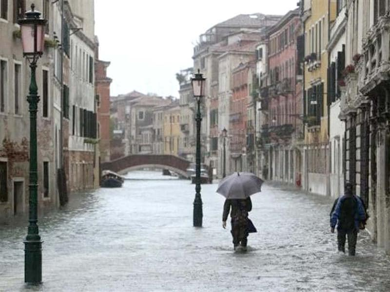 People walk in a flooded street during a period of seasonal high water in Venice November 11, 2012. Reuters/Manuel Silvestri