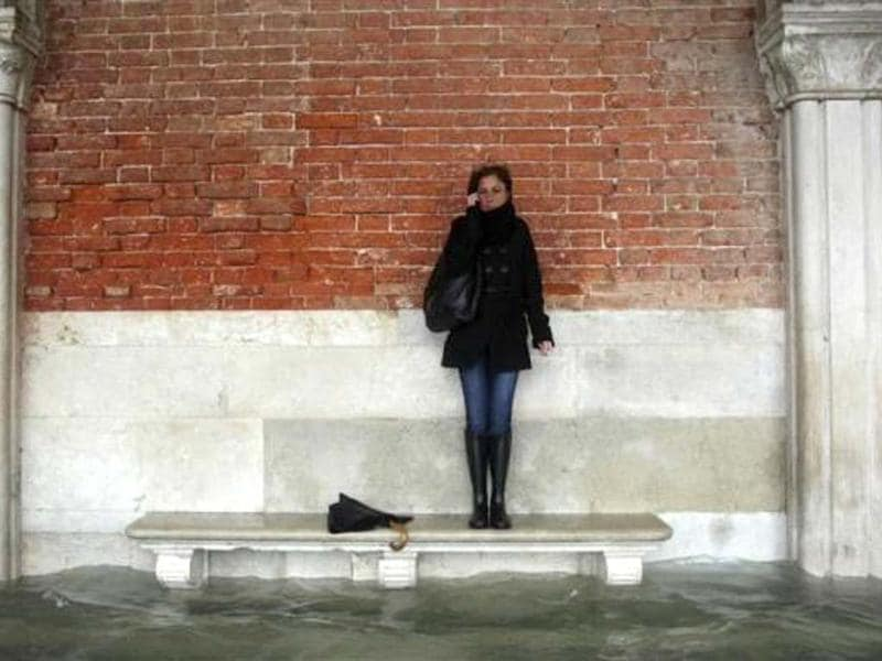 A woman stands on a bench above a flooded street during a period of seasonal high water in Venice November 11, 2012. Reuters/Manuel Silvestri