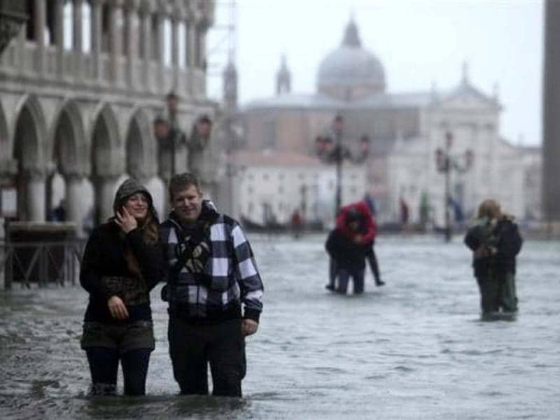 People walk through a flooded street during a period of seasonal high water in Venice November 11, 2012. The water level in the canal city rose to 149 cm (59 inches) above normal, according to local monitoring institute Center Weather Warnings and Tides. Reuters/Manuel Silvestri