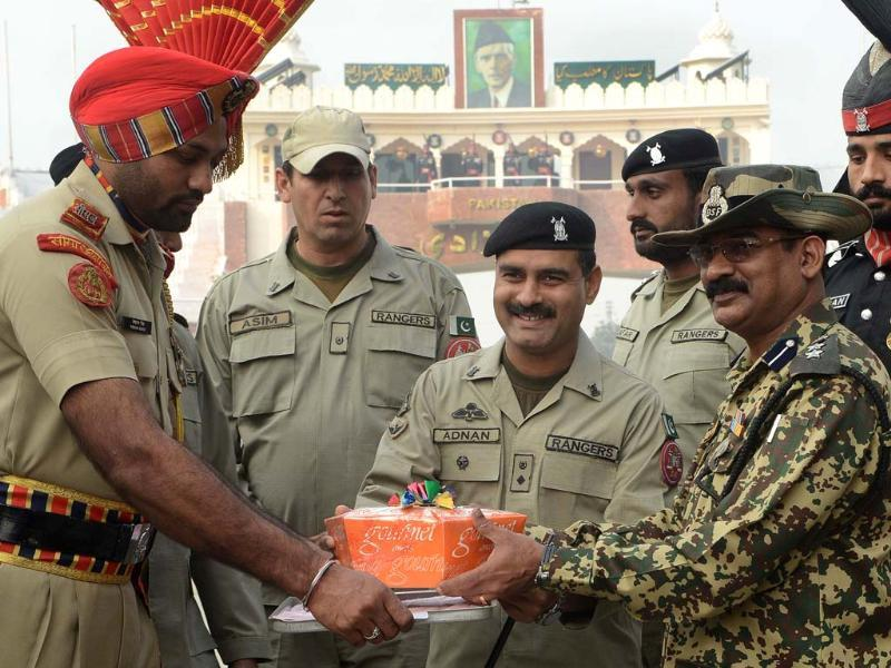 Pakistani Rangers wing commander Adnan (C) presents a box of sweets to Indian Border Security Force (BSF) Deputy Inspector General (DIG), Baby Joseph (2R) on Diwali at the India-Pakistan Wagah Border. AFP PHOTO