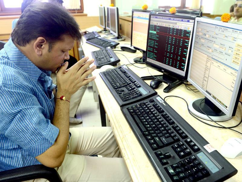 A stock trader prays in front of his trading terminal before Muhurat Trading - a special trading session on the occasion of Diwali. AFP PHOTO