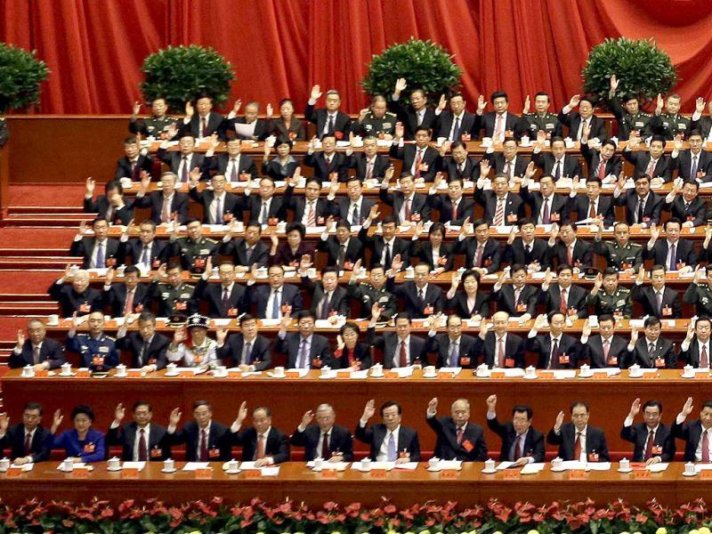 China's leaders raise their hands to show approval for a work report at the closing ceremony for the 18th Communist Party Congress held at the Great Hall of the People in Beijing. (AP Photo)