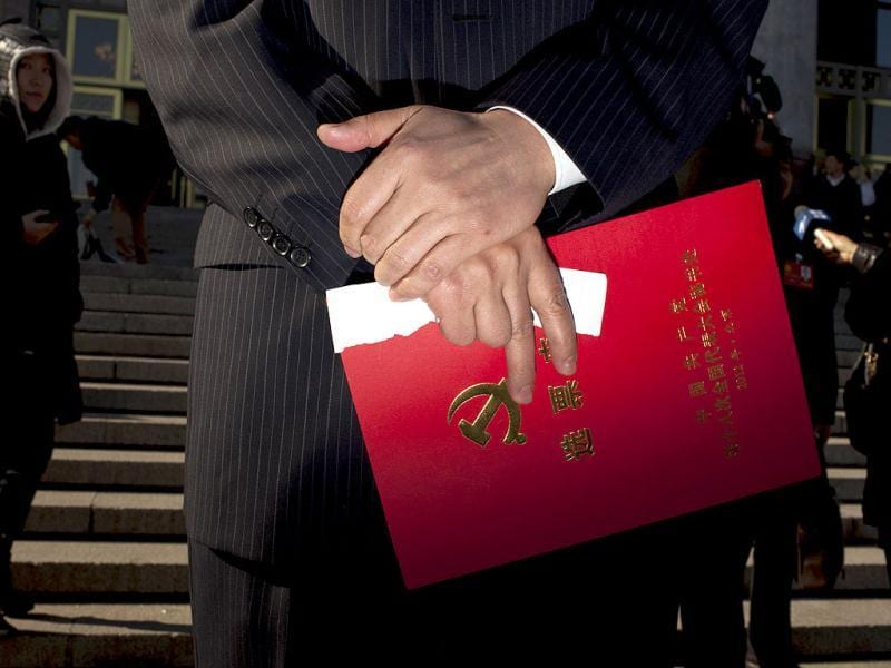 A Chinese Communist Party delegate holds a red voting ticket holder while leaving the Great Hall of the People with other delegates after the closing ceremony for the 18th Communist Party Congress in Beijing. (AP Photo)