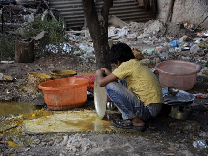 A boy washes utensils by the road in New Delhi, on the occasion of childrens day. Hindustan Times