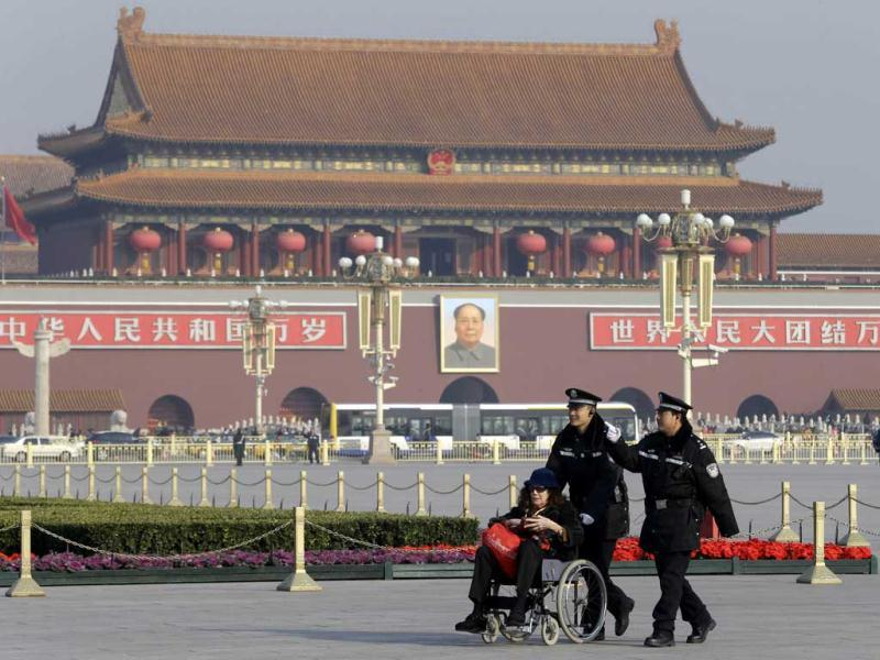 Chinese police officers push an elderly foreigner towards the Great Hall of the People to attend a press event introducing China's new leaders, a day after the closing of the 18th Communist Party Congress in Beijing. AP photo