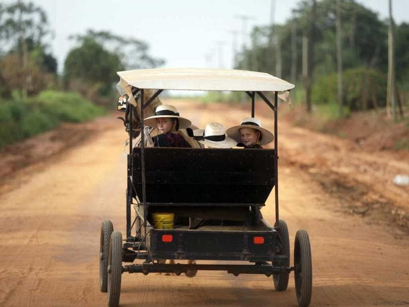 Mennonite girls look back as they ride in a horse drawn cart along a dirt road near the town of Nueva Durango in the department of San Pedro in Paraguay. AP photo