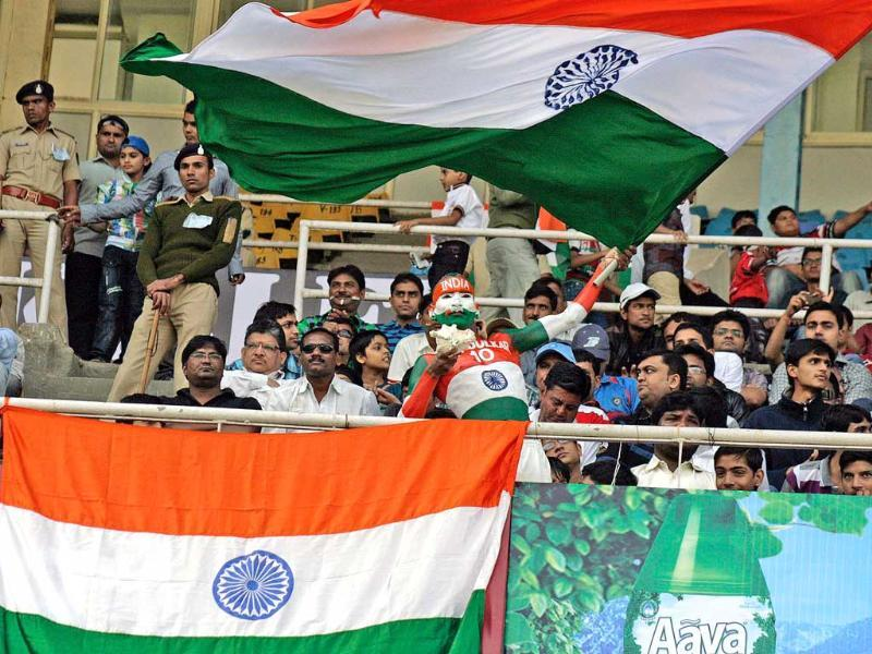 Cricket fans wave the tricolour on the first day of first test match against England at Sardar Patel Motera stadium in Ahmedabad. UNI
