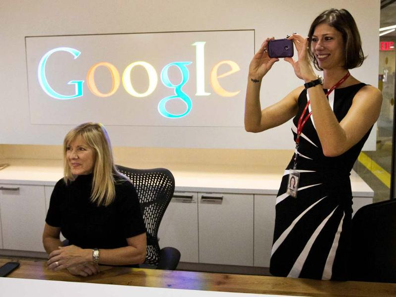 Google employee Andrea Janus takes a picture with her phone as her co-worker Tracy McNeilly looks on at the new Google office in Toronto, November 13, 2012. Reuters/Mark Blinch