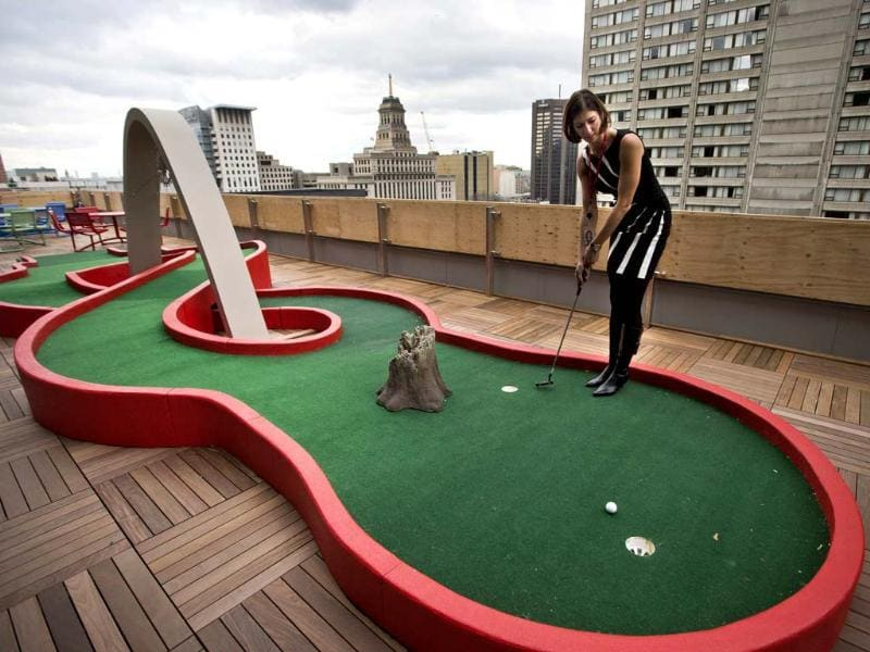 Google employee Andrea Janus demonstrates the use of the mini-putt green on the balcony at the new Google office in Toronto, November 13, 2012. Reuters/Mark Blinch