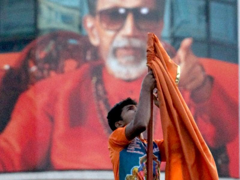 A Shiv Sena worker removes the party flag from the Sena Bhavan after the news of Balasaheb Thackeray's death was announced in Mumbai. PTI/Santosh Hirlekar