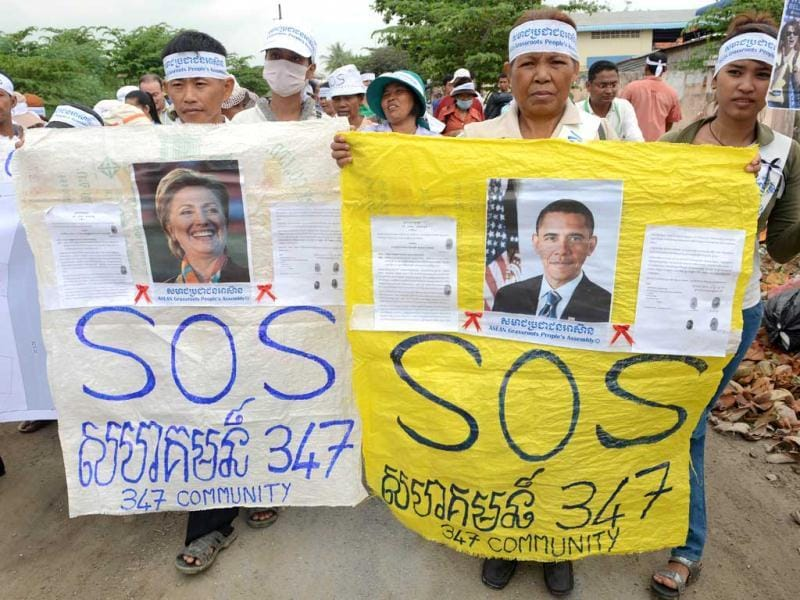 Cambodian people from Boeung Kak lake community hold banners with portraits of US President Barack Obama (R) and US Secretary of State Hilary Clinton during a protest at their community in Phnom Penh. (AFP Photo)