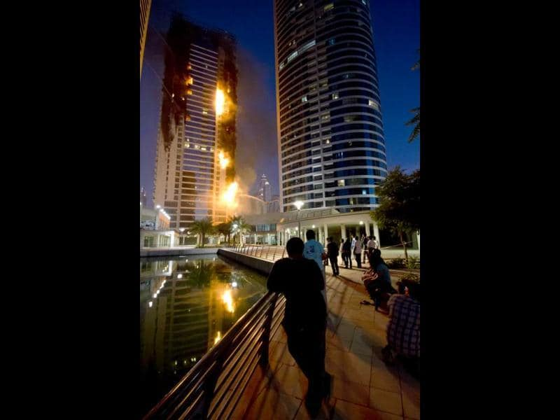 People watch flames engulf a portion of Tamweel residential tower at Jumeirah Lakes Towers, in Dubai. (AP Photo)