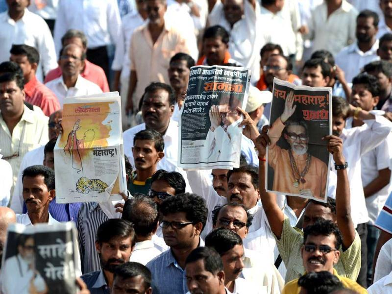 Supporters hold up Shiv Sena's official newsletter 'Saamna' with the front page news of the demise of Shiv Sena party chief Bal Thackeray during his funeral procession in Mumbai. AFP Photo