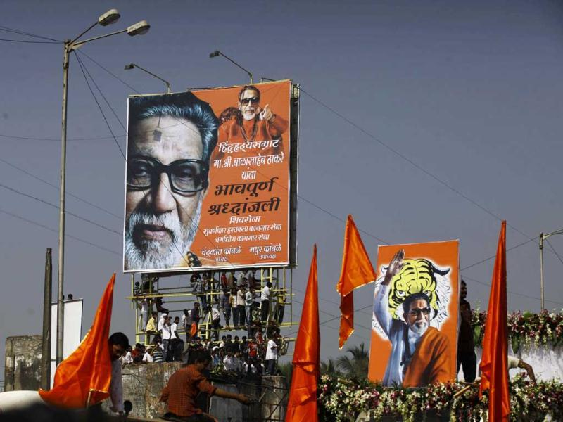 Shiv Sena chief Bal Thackeray's supporters, climb on a billboard displaying his picture, during his funeral in Mumbai. AP Photo
