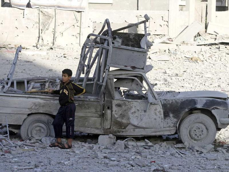 A Palestinian boy stands next to a destroyed car after an Israeli airstrike in the Jabaliya refugee camp, northern Gaza Strip. AP