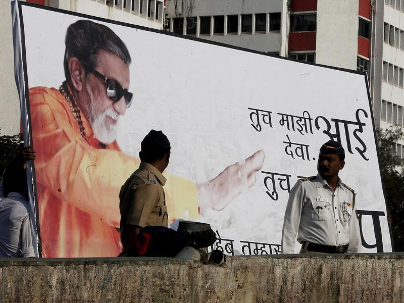 Shiv Saniks hang a hoarding as crowd gathered for the funeral of Shiv Sena leader Bal Thackeray in Mumbai. HT/Anshuman Poyrekar