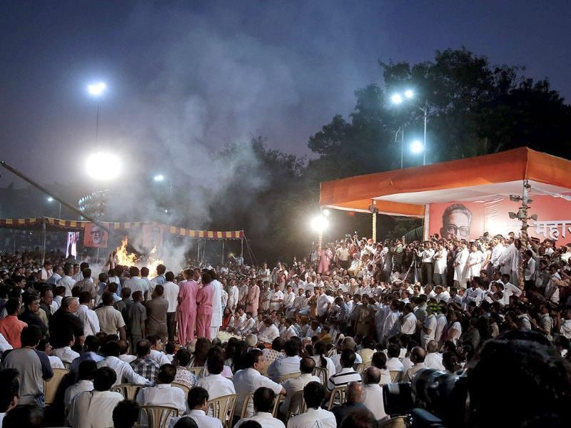 Smoke rises from the cremation pyre of Shiv Sena leader Bal Thackeray as family members, dignitaries and Shiv Sena party members watch during his funeral in Mumbai. Reuters/Vivek Prakash