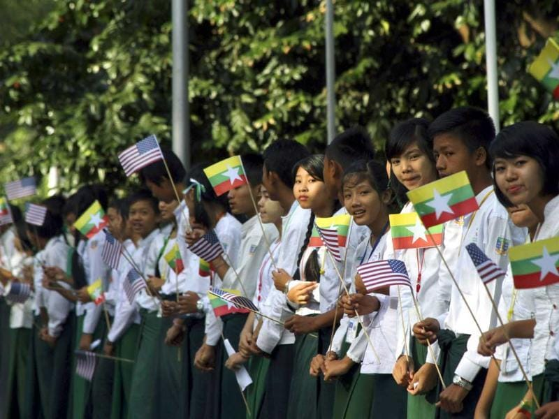 Myanmar students wave miniature Myanmar and American flags as they wait to welcome US President Barack Obama at Yangon International Airport on Monday, Nov. 19, 2012, in Yangon, Myanmar. (AP Photo/Khin Maung Win)