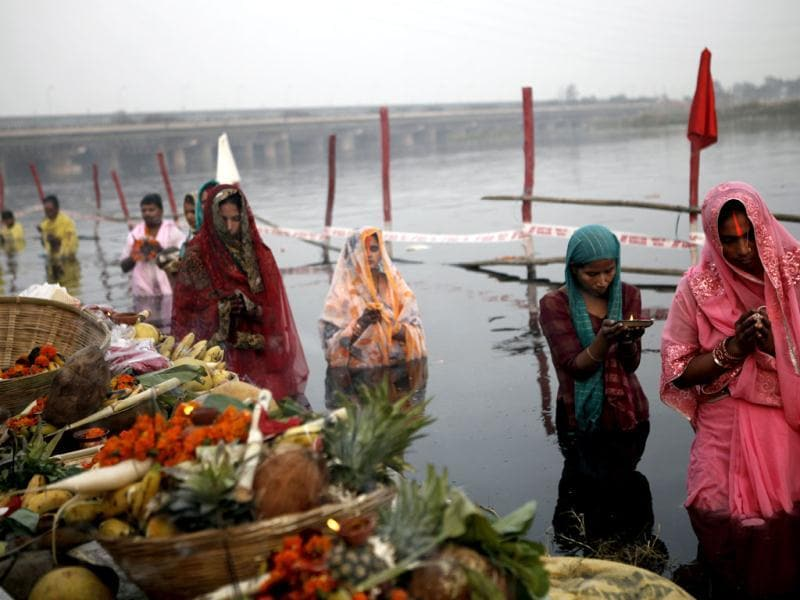 Devotees offer prayers to Lord Sun on the occasion of Chhath Puja at Yamuna ghat in New Delhi. HT Photo/M Zhazo