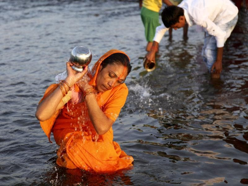 A devotee performs rituals at River Tawi during Chhath Puja in Jammu. AP Photo/Channi Anand