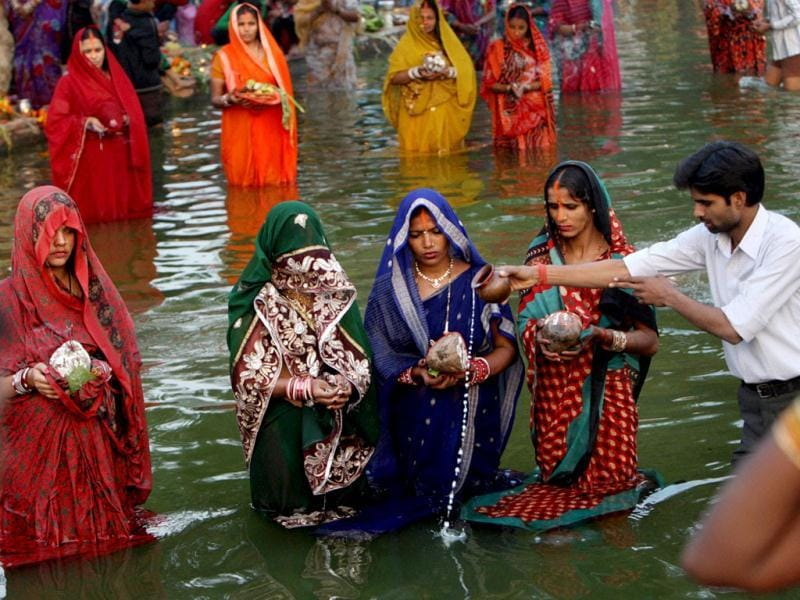 Women offer prayers to Lord Sun on the occasion of Chhath Puja near India Gate in New Delhi. PTI Photo/Subhav Shukla