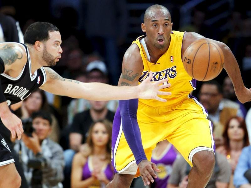 Los Angeles Lakers' Kobe Bryant and Brooklyn Nets' Deron Williams go after a loose ball in the first half of an NBA basketball game in Los Angeles. AP/Jae C Hong