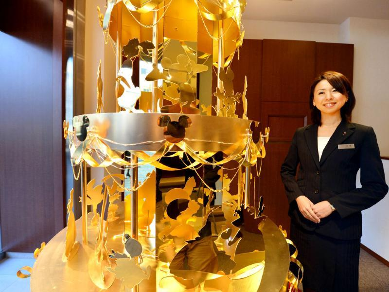An employee of Japan's jeweler Ginza Tanaka introduces the 350 million yen (4,270,000 USD) Disney Gold Christmas Tree which is 2.4 meters in height and features 50 Disney characters made of gold, in Tokyo. AFP/Kazuhiro Nogi