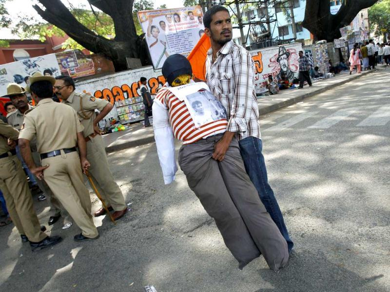 Policemen stand guard as an activist of Akhil Bharatiya Vidyarthi Parishad or All Indian Student Council, carries an effigy of Mohammed Ajmal Kasab, the lone surviving gunman from the 2008 terror attacks on Mumbai, before it was burned to celebrate his execution, in Bangalore. (AP Photo/Aijaz Rahi)