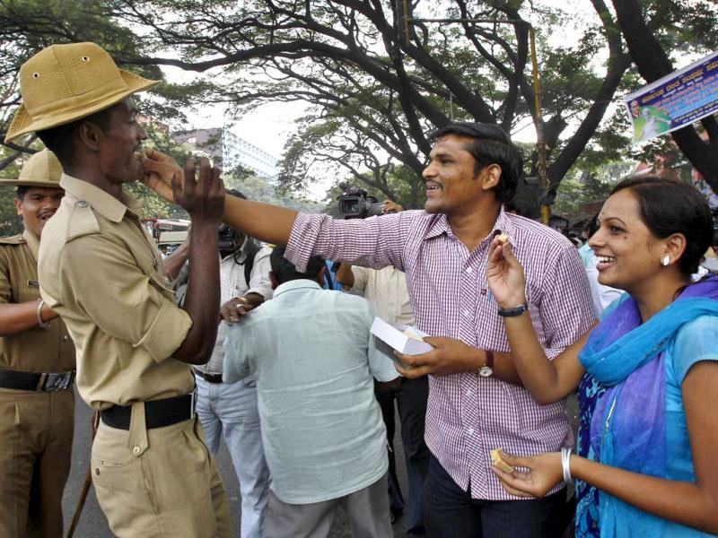 Activists of Akhil Bharatiya Vidyarthi Parishad, or All Indian Student Council, offer sweets to a policeman to celebrate on hearing the news that Mohammed Ajmal Kasab, the lone surviving gunman from the 2008 terror attacks on Mumbai, was executed, in Bangalore. (AP Photo/ Aijaz Rahi)