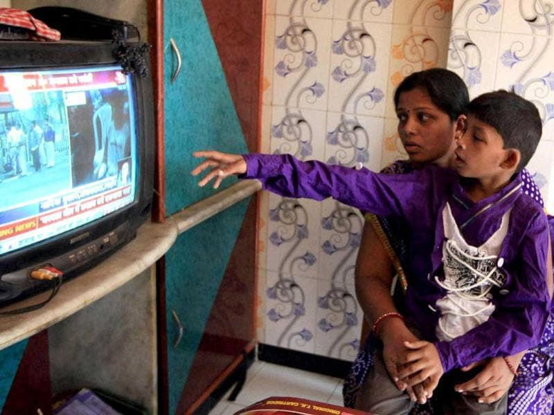 Karuna Waghela, widow of a 2008 Mumbai terror attack's victim, with her son, watching news of Ajmal Kasab's death on TV. (PTI Photo)