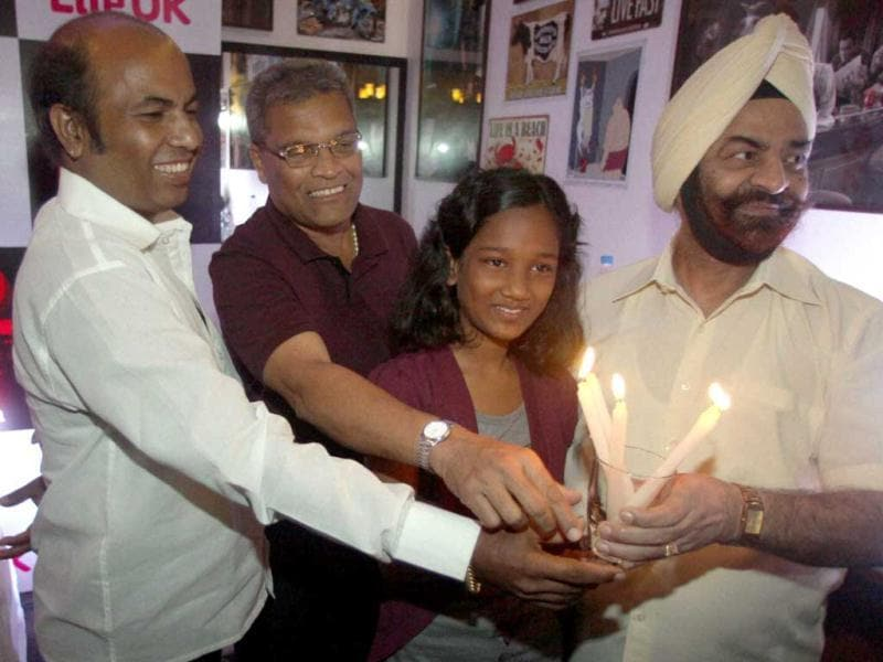 Photojournalist Sebastian D'Souza who took Ajmal Kasab's picture, Devika Rotwana who was injured by Kasab's bullet and Railway announcer Vishnu Zende who helped people to escape from the attack, hold candles with former Director General of Police, P S Pasricha during a felicitation program in Mumbai after Kasab was executed. (PTI Photo)