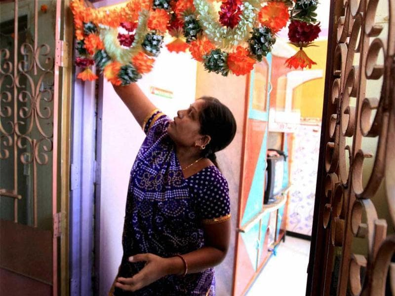 Karuna Waghela, widow of a 26/11 Mumbai attack's victim, arranges a garland at her door in Mumbai after Ajmal Kasab's execution. (PTI Photo)