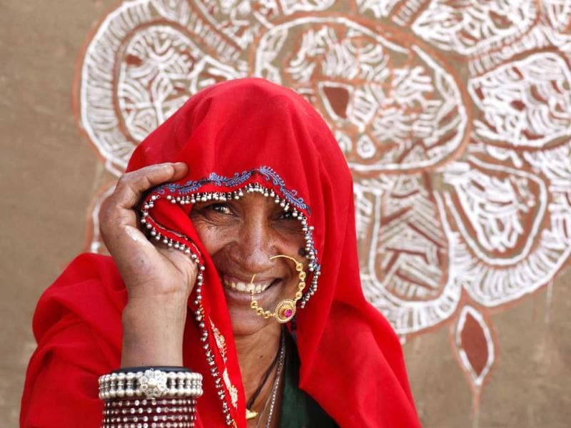 A Rajasthani woman looks through her veil after a wall painting competition at the annual cattle fair in Pushkar, Rajasthan. AP