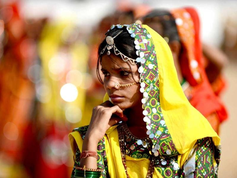 A young woman dressed in traditional Rajasthani clothing waits for the start of a traditional dance presentation at the camel fair grounds in the outskirts of the small town of Pushkar. AFP