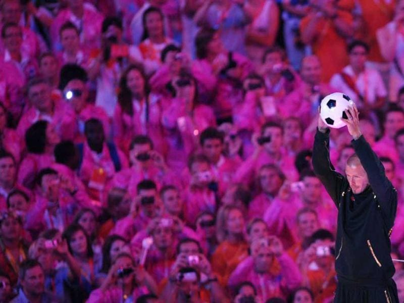 David Beckham holds a ball towards the crowd during the closing ceremony for the 2008 Beijing Olympic Games at the National Stadium also know as the