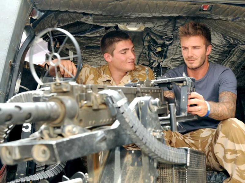 is being shown the mounted heavy machine Gun on an Army Lynx helicopter by Lance Corporal Chandler, 9 Army Air Corps, during a visit to Camp Bastion, in Afghanistan on May 22, 2010. AFP Photo/ministry of defence