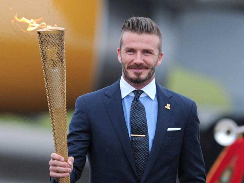 David Beckham carries the Olympic torch as it arrives at RNAS Culdrose air base in Cornwall, south-west England, May 18, 2012. AFP Photo