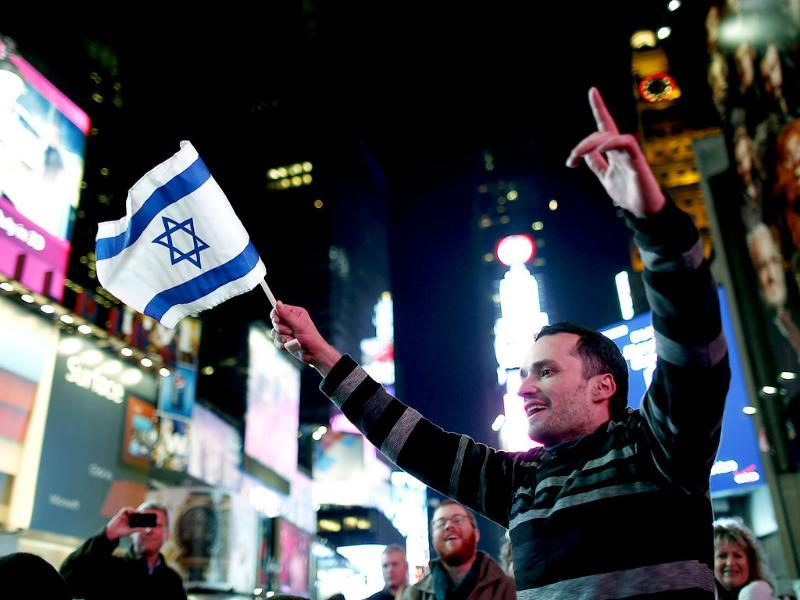 A pro-Israel supporter waves an Israeli flag as he gathers with others in Times Square to celebrate the ceasefire agreement between Israel and Hamas, in New York. Reuters/Carlo Allegri