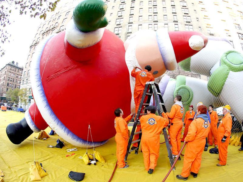Workers fill the beard of a balloon in the shape of Santa Claus, with helium, ahead of the Macy's Thanksgiving Parade in New York. Reuters/Carlo Allegri
