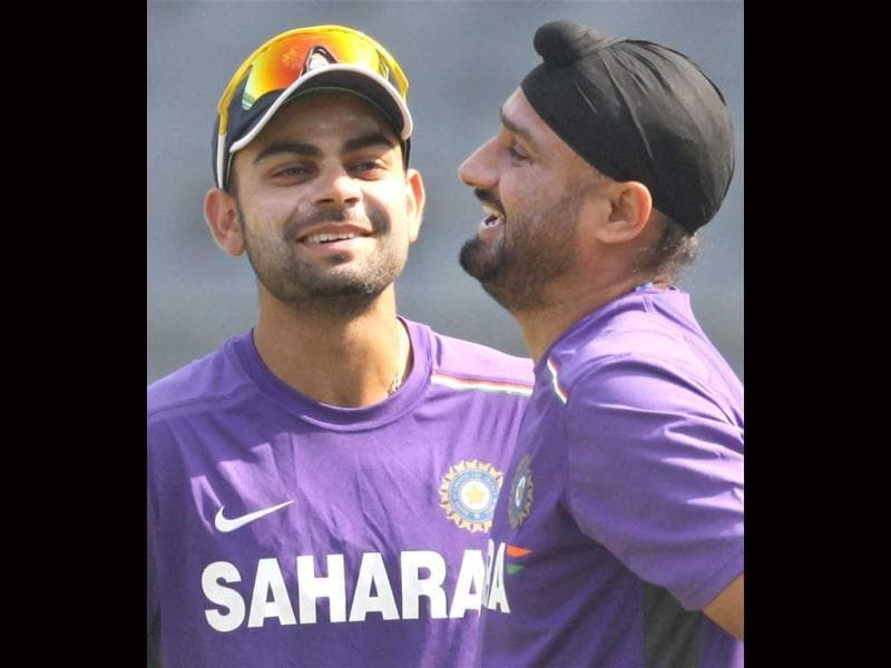 Harbhajan Singh and Virat Kohli share a light moment during a practice session at Wankhade Stadium in Mumbai. PTI