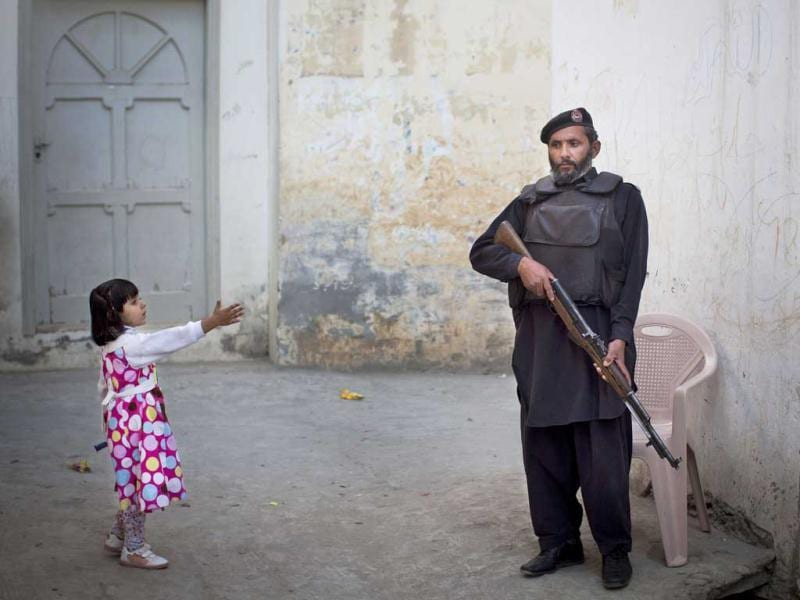 A young girl reaches out to greet a Pakistani policeman securing the road outside Kainat Riaz's home in Mingora, Swat Valley, Pakistan. AP/Anja Niedringhaus