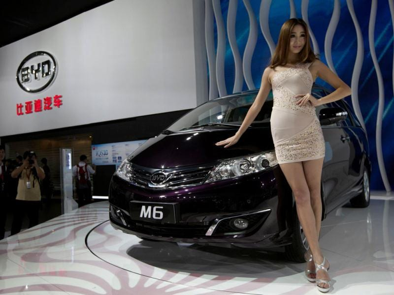 A model poses next to a M6, a car by Chinese automaker BYD Auto, during the media preview of the 10th China International Automobile Exhibition in Guangzhou. Reuters/Tyrone Siu