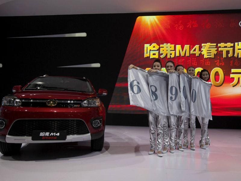 Staff members display the price of the Great Wall Motors Haval M4 mini SUV during the media preview of the 10th China International Automobile Exhibition in Guangzhou. Reuters/Tyrone Siu