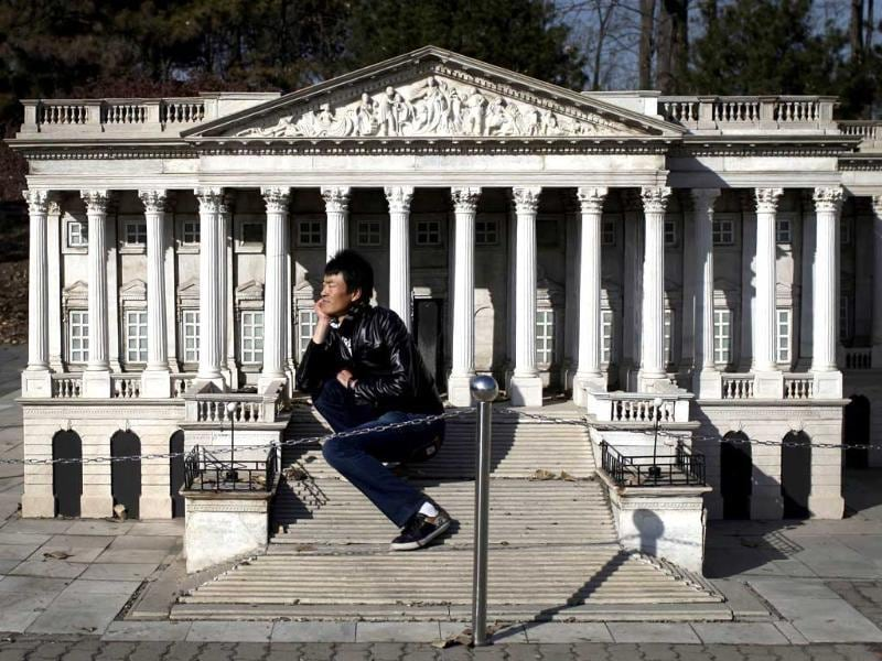 A tourist sits on the steps of the mini replica of the United States Capitol in Beijing World Park, in the southwestern suburb of Beijing. Photo: AFP