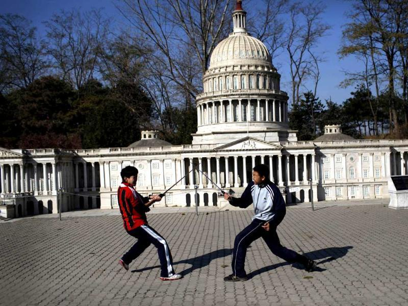 Two boys play sword in front of the mini replica of the United States Capitol in Beijing World Park, in the southwestern suburb of Beijing. Photo: AFP